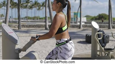Sporty woman working out on machines
