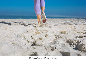 Sporty womans feet jogging on the sand on a sunny day
