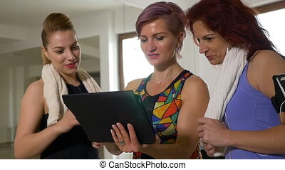 Sporty women in gym studio using tablet for training weight...
