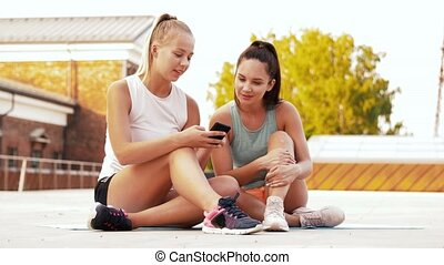 sporty women or friends with smartphone on rooftop -...