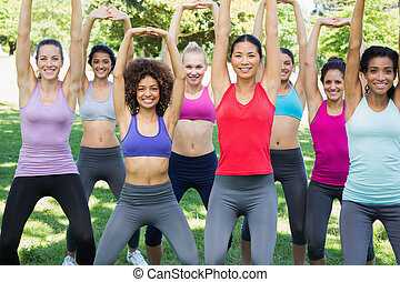 Sporty women stretching at park - Portrait of sporty women...