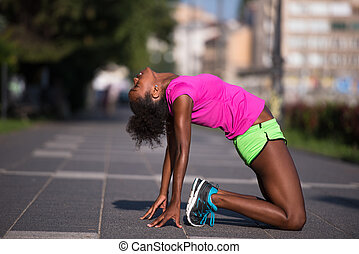 sporty young african american woman stretching outdoors