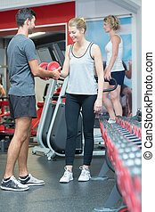 sporty young couple with dumbbells in gym