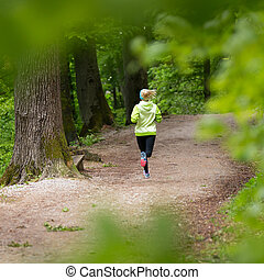 Sporty young female runner in the forest. - Sporty young...