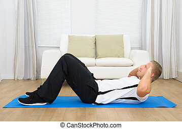 Sporty Young Man Doing Sits-up On Exercise Mat At Home