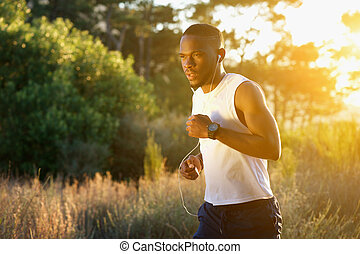 Sporty young man running outdoors in nature