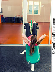 Sporty young woman doing sit-up using training apparatus in ...