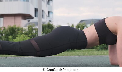 Sporty Young woman doing strap exercise training at street side view. Young active girl with perfect body enjoying athletic activity in slow motion