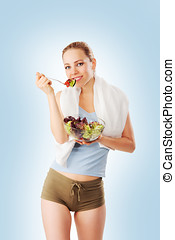 Sporty young woman eating salad