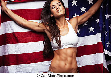 Sporty young woman holding American flag