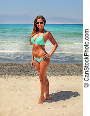 Sporty young woman in light blue bikini, wearing sunglasses, sun tanned, smiling, wind in her hair, standing on beach with azure sea behind her.