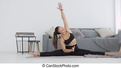 Sporty young woman is doing stretching exercises sitting on mat leaning to legs.