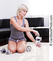 Sporty young woman is drinking mineral water.