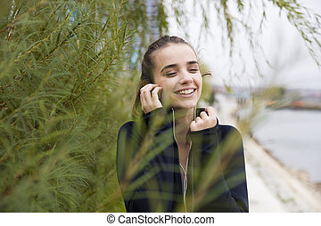 Sporty young woman listening music outdoor