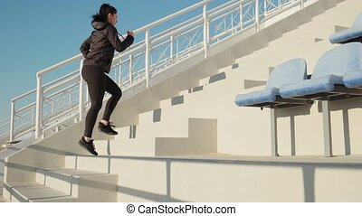 Sporty young woman makes cardio training running up on...