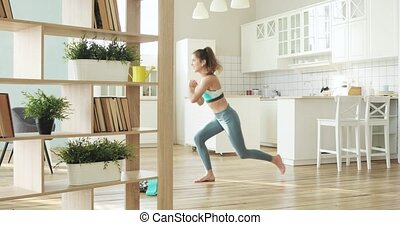 Sporty young woman making lunge squat exercise in living ...