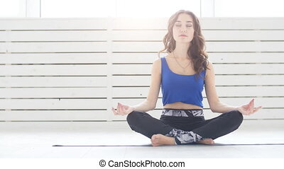 Sporty young woman practicing yoga, sitting in Half Lotus...