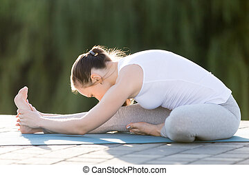 Sporty young woman practicing yoga, sitting in Head to Knee Forward Bend exercise, Janu Sirsasana pose, working out, wearing sportswear, outdoor, sunny summer day background