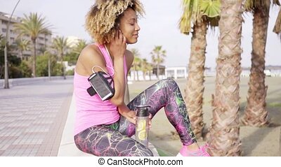 Sporty young woman relaxing with bottled water