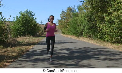 Sporty young woman runner jogging on the road