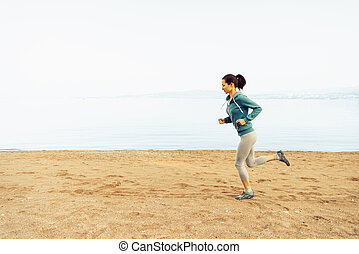 Sporty young woman running on sand beach