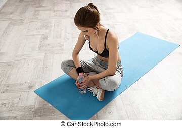 Sporty young woman sitting on the yoga mat with bottle of water
