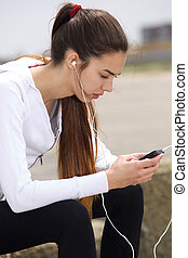 Sporty young woman sitting outside with headphones
