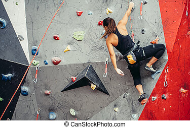 Sporty young woman training in a colorful climbing gym. Free...