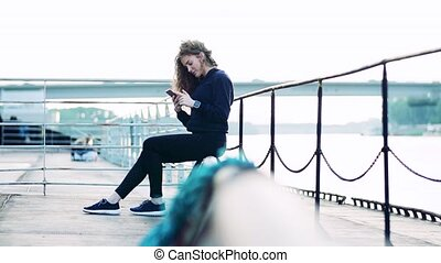 Sporty young woman using smartphone by the river in the...