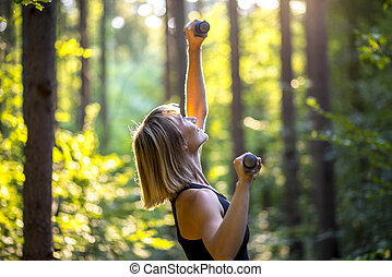 Sporty young woman working out with weights