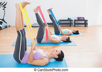 Sporty young women with exercise bands in fitness studio