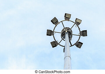 Spot-light tower at the road on blue sky