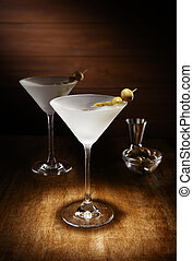 Spotlight on 2 Chilled martinis, with olives, shot on a dark wooden background