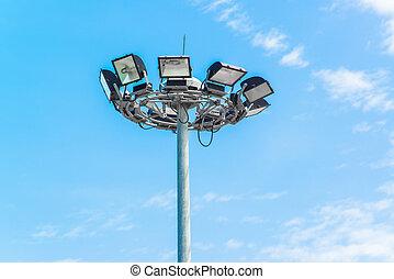 Spotlight tower against blue sky
