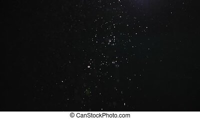 Spotlight with a stream of dust particles on a black background. Sparkling particles rotate randomly in the air with blurry bokeh. Beautiful fabulous background. Close up in slow motion