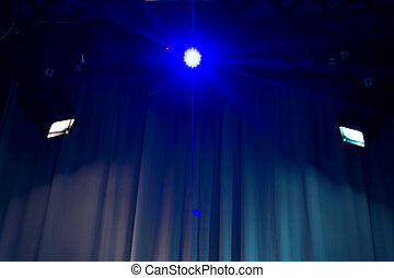 Spotlights shining on an empty venue with a white curtained...