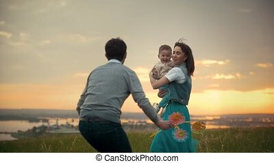 Spouses with a child walking outdoor at sunset - slow-motion