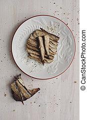 Sprats on white dish and bitten sandwich