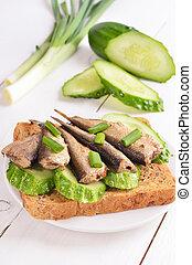 Sprats sandwich on white plate