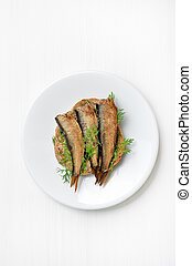 Sprats sandwiches on white plate