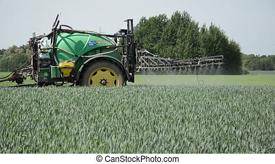 spray crop - tractor pulls tank with fertilizer from the...
