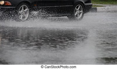 spray from the car - Car rides on big water in the rain