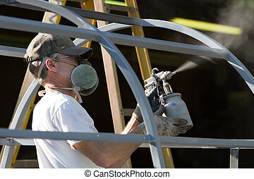 Spray Painter Man - Construction worker spray paints while...