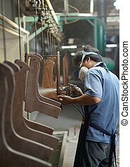 Factory worker spray painting furniture parts at an assembly line
