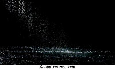 Spray spatters rain fall against on the water surface which glow. Black background. White neon lighting in dark studio. Slow motion