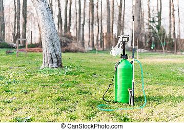 sprayer - green sprayer on spring garden