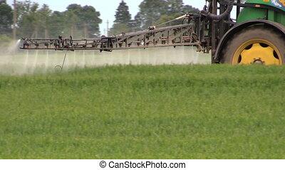 sprayer tractor crop grow - Spraying wheat crops field with...