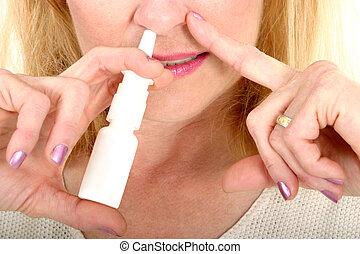 Spraying Nasal Spray in Nose - Woman spraying nasal spray in...