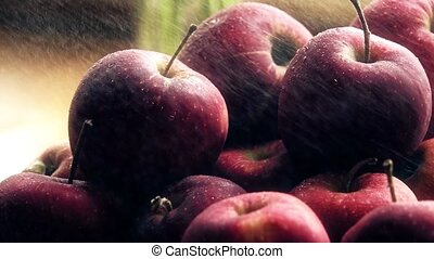 Spraying water over fresh ripe red apples on a wooden table. Close-up slow motion shot