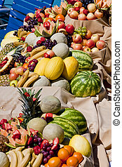 A spread of many bruits and vegetables on an outdoor buffet